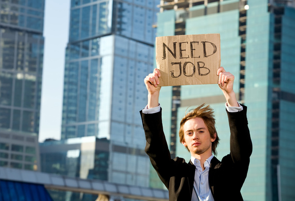 Crisis. Young businessman holding sign Need Job outdoors