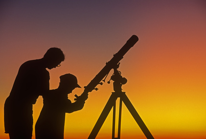 A father demonstrates to his child how to use a telescope
