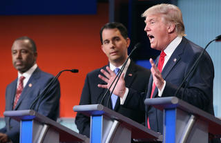 CLEVELAND, OH - AUGUST 06: Republican presidential candidates (L-R) Ben Carson, Wisconsin Gov. Scott Walker and Donald Trump participate in the first prime-time presidential debate hosted by FOX News and Facebook at the Quicken Loans Arena August 6, 2015 in Cleveland, Ohio. The top-ten GOP candidates were selected to participate in the debate based on their rank in an average of the five most recent national political polls. Chip Somodevilla/Getty Images/AFP