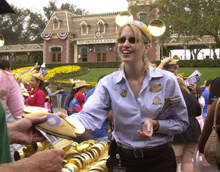 Disney cast member Annika Chase greets guests arriving at the theme park's turnstyles on the morning of Disneyland's 50th Birthday Event, July 17, 2005. Each guest to the park received a free pair of golden mouse ears to commemorate the date. (Photograph by Tammy Lechner/Disneyland Resort©)
