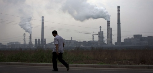 In this May 29, 2015 photo, a man walks past a coal-powered steel plant in Tianjin, China. India and China would need to reduce average levels of tiny, inhalable particulate matter called PM 2.5 by 20 to 30 percent merely to offset their demographic changes and keep mortality rates steady a new study shows. (AP Photo/Andy Wong)/XAW103/398685012788/MAY 29, 2015 PHOTO, HOLD FOR STORY CHINA AIR POLLUTION MORTALITY BY KATY DAIGLE/1506161234