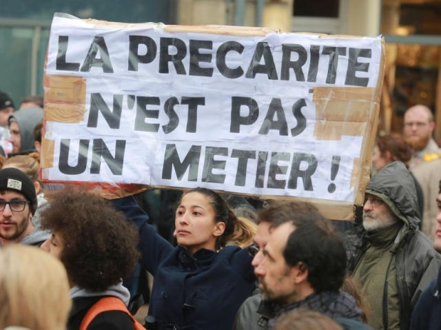 "A high school student holds a placard reading ""Precariousness is not a job"" during a demonstration against the French government's planned labour law reforms on March 31, 2016 in Bordeaux.   France faced fresh protests over labour reforms just a day after the beleaguered government of President Francois Hollande was forced into an embarrassing U-turn over constitutional changes. / AFP / NICOLAS TUCAT"