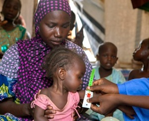 On 25 May, (right, partially visible) a volunteer community mobilizer, Yagana Abba Kari, using a mid-upper arm circumference (MUAC) band, measures the arm of a girl sitting on a woman's lap, during a nutrition screening for children in the Dalori camp for internally displaced people, in the north-eastern city of Maiduguri in Borno State. The red section of the armband indicates that the child is severely malnourished. At end May 2015 in Nigeria, 15.5 million people, including 7.3 million children, are affected by the continuing crisis in the country's north-eastern region. More than 1.3 million Nigerians in the three states affected – Adamawa, Yobe and Borno – have fled their homes as a result of violence and attacks by Boko Haram insurgents that have escalated since the beginning of 2015. Many of the displaced, most of whom are children and women, are sheltering in host communities that have limited resources, and in formal and informal camps. All are in urgent need of basic supplies, health and nutrition services, and critical water, sanitation and hygiene (WASH) support to prevent the spread of disease. An estimated 200,000 people have also fled to neighbouring Cameroon, Chad and the Niger, further straining already vulnerable communities. The impact of the crisis on children and women is of particular concern. Many of them have lost their homes and belongings – escaping with only the clothing they were wearing; and some have walked for days – or even weeks – to find refuge. Many children in the region have been traumatized and are in need of psychosocial support. They have witnessed violence and atrocities, including seeing parents and siblings slaughtered by Boko Haram insurgents; and have been exposed to or have experienced violence and brutality. Their homes have been burned and their schools have been damaged or destroyed during the attacks. The insurgency has also created a larger humanitarian crisis in the region. UNICEF is working with th