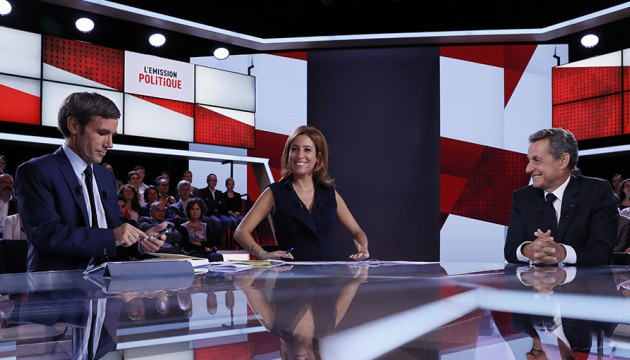 """French journalists and TV hosts David Pujadas (L) and Lea Salame (C) sit with their guest former French president and candidate for the right-wing Les Republicains (LR) party primary ahead of the 2017 presidential election, Nicolas Sarkozy (C), on a TV set before taking part in  the new show """"L'Emission politique"""" (The Politics Show) on French TV channel France 2, on September 15, 2016, in Saint-Cloud, west of Paris. / AFP PHOTO / Thomas SAMSON"""