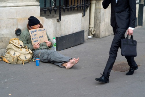 A homeless person begs on March 14, 2015 in Paris. AFP PHOTO / KENZO TRIBOUILLARD