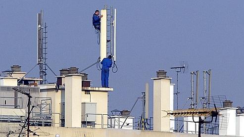 des techniciens installent des relais téléphoniques sur le toit d'un immeuble parisien, le 20 mars 2003. La ville de Paris a signé le même jour une charte avec les trois opérateurs de téléphone mobile - SFR, Orange et Bouygues - pour encadrer et mieux intégrer ces émetteurs de champs électromagnétiques.     AFP PHOTO / JACQUES DEMARTHON